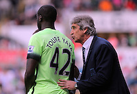 ( L-R ) Yaya Toure of Manchester City is spoken to by Manuel Pellegrini, Manager of Manchester City during the Swansea City FC v Manchester City Premier League game at the Liberty Stadium, Swansea, Wales, UK, Sunday 15 May 2016
