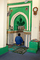 Kizimkazi, Zanzibar, Tanzania.  Imam Yusuf Ratib Ashkina Praying in Mihrab of the Mosque, with inscription dated to 1107A.D.  The Kufic inscription attributes the founding of the mosque to Persian settlers.  This is the oldest dated Arabic inscription on the East African coast.