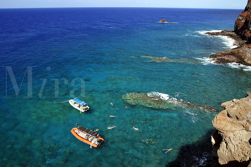 Snorkelers are enjoying the sights on this Hawaiian reef off the backside of Lanai. Sharkfin Rock can be seen in the background. Lanai, Hawaii.