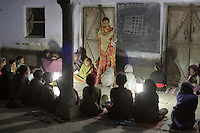 A night school in the village of Cheeri, lit by solar lanterns. Most of the students are girls from lower caste / untouchable backgrounds who must work in the fields during the day. Without the solar lanterns the schools would not be able to function. The teacher's name is Kishan Kanwar, age 32. She comes from a Rajput (upper caste) family. When she decided to work professionally as a teacher it created a scandal in her town because women of her caste are not supposed to mix with anyone from lower castes...