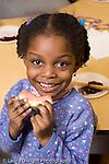 Preschool 4-5 year olds closeup of girl eating piece of fruit watermelon at school snack vertical