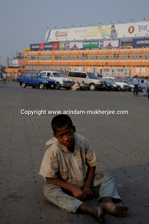 Alamgir dazed from drugs sitting on a street at the Sealdah railway premises. He is staying here for last 6 years from the time he ran away from his home due to domestic violence and poverty. As per his version his father was a drunkard and used to beat his mother for no reason. His father even could not earn enough money to buy food for their big family. Due to this traumatic situation he ran away from house at the age of seven. Ever since, the Sealdah railway station in Kolkata has been his home. As far as company is concerned, he had not much reason to miss his family. There are around 500 children, from 5 to 16 years, who live in the premises of Kolkata's second largest train terminus. Most of them addicted to Brown Sugar and sniffing industrial adhesive Dendrite. They say they don't feel hungry if they take the drugs. Their presence is conspicuous, even in a place that registers an average footfall of 1.4 million on weekdays. Their activities cover a wide range, from begging, to pulling handcarts, to petty theft, to selling odds and ends on the platform or on trains. The money, earned or ill-gotten as the case may be, is spent in procuring heroin, brown sugar, cocaine, and tubes of Dendrite. Calcutta, West Bengal, India. Arindam Mukherjee