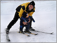 A young child/toddler has his first lesson in snow skiing. Father is teaching son how to ski. Photo taken in Pennsylvania. Model released image.