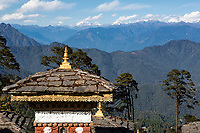 Punakha, Bhutan.  Chortens (Shrines) at a Mountain Pass in Himalayan Foothills; Himalayan Mountains in the Distance.