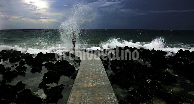 A man watches the skyline on the shore during a storm in Roatan , Honduras on August, 20, 2007..Born in Argentina, photographer Ivan Pisarenko in 2005  decided to ride his motorcycle across the American continent. While traveling Ivan is gathering an exceptional photographic document on the more diverse corners of the region. Archivolatino will publish several stories by this talented young photographer..Closer look at  Ivan's page www.americaendosruedas.com...