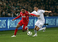 SWANSEA, WALES - MARCH 16: Jack Cork of Swansea (R) closely follows Raheem Sterling of Liverpool (L) during the Premier League match between Swansea City and Liverpool at the Liberty Stadium on March 16, 2015 in Swansea, Wales