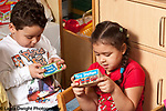 Education preschool 3-4 year olds pretend play boy and girl pretending boys are handheld electronic game toys