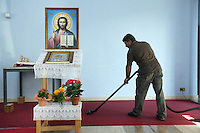 Italy. Lazio region. Guidonia. A man, romanian citizen, uses a vacuum cleaner on the red carpet at the end of the orthodox sunday mass. Icon of the Lord Jesus. Flowers' pots. Romanian immigration. Guidonia is a town and comune in the province of Rome. 02.10.2011 © 2011 Didier Ruef