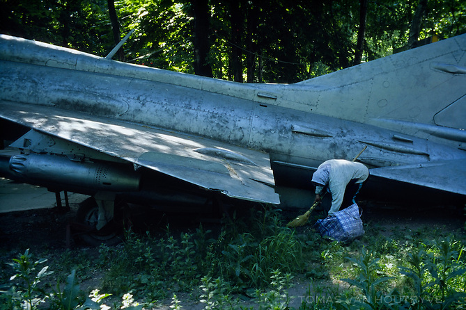 A woman cleans under an old Soviet fighter plane inside museum garden full of Soviet war machines in the center of Chisinau, Moldova on 28 May 2009.
