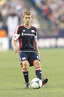 New England Revolution midfielder Scott Caldwell (6) passes the ball.  In a Major League Soccer (MLS) match, Houston Dynamo (orange) defeated the New England Revolution (blue), 2-1, at Gillette Stadium on July 13, 2013.