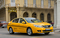 Havana, Cuba - A modern taxi cab passes in front of Hotel Plaza near Parque Central.