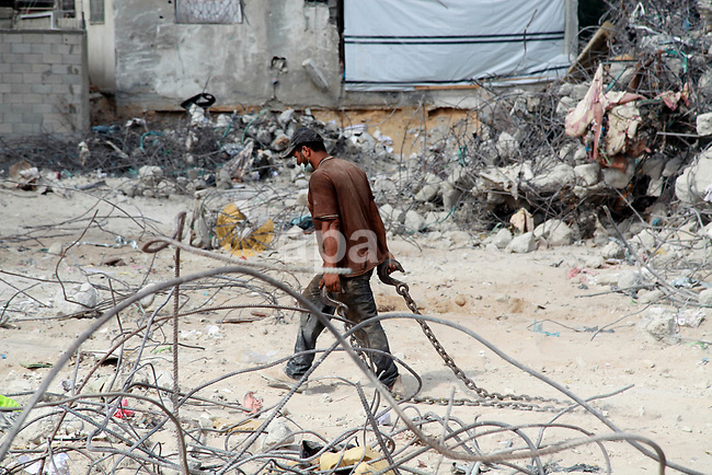 Palestinian workers remove the rubble of Jala' Tower recently destroyed by Israeli strikes in Gaza City, on August 8, 2021. Al-Sisi also promised $500 million for rebuilding Gaza, and gave directives to Egyptian state institutions to provide all that is needed to accelerate reconstruction and completion. Photo by Omar Ashtawy