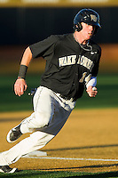 Conor Keniry (14) of the Wake Forest Demon Deacons rounds third base against the West Virginia Mountaineers at Wake Forest Baseball Park on February 24, 2013 in Winston-Salem, North Carolina.  The Demon Deacons defeated the Mountaineers 11-3.  (Brian Westerholt/Four Seam Images)