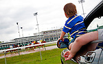 Preston Dossey, 19 months, squeezes out the window of his father Joshua's Dodge Charger to see the horses race by Wednesday afternoon at Churchill Downs.  Joshua is a racetrack employee who usually works 9 to 5, but was off today. The whole family decided to come watch the races.  Already an aficionado, Preston has been to the track close to a dozen times.