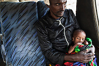 A father craddles his severely malnourished child on a bus provided by UNHCR and IOM to  move a group of stranded vulnerable refugees from Hamey, Kenya near the Somalia border refugee camps near Dadaab, Kenya. Most refugees make the journey from the border to the camps by foot at great peril. The roads are lined with bandits and many women report  being raped during the trek.