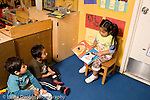 "Education Preschool 3-4 year olds pretend play girl sitting in chair playing teacher to two boys who are listing to her ""reading"" of picture book horizontal"