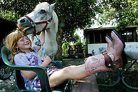 """After feeding her horse lunch, Leona Klement, 6, of Geneva, spends some fun time with her pony """"Sundance"""" near the barn Thursday afternoon, May 15, 2003. The youngster feeds her horse twice a day, and enjoys going on rides with her pink """"cowgirl"""" boots her grandmother bought her.(Kelly Jordan)"""