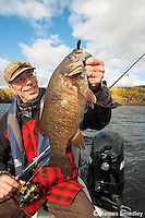 Angler holding up a large bass in a fishing boat.