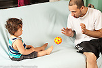 Infant development 12 month old baby boy woth father playing reciprocal game throwing ball back and forth