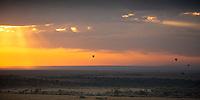 Hot air balloons flying over Masai Mara national park savanna during a beautiful orange sunrise at the border of Kenya and Tanzania, in Africa
