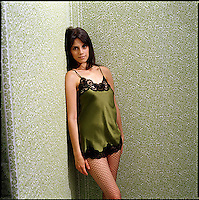 Woman wearing negligee against green patterned wallpaper background<br />