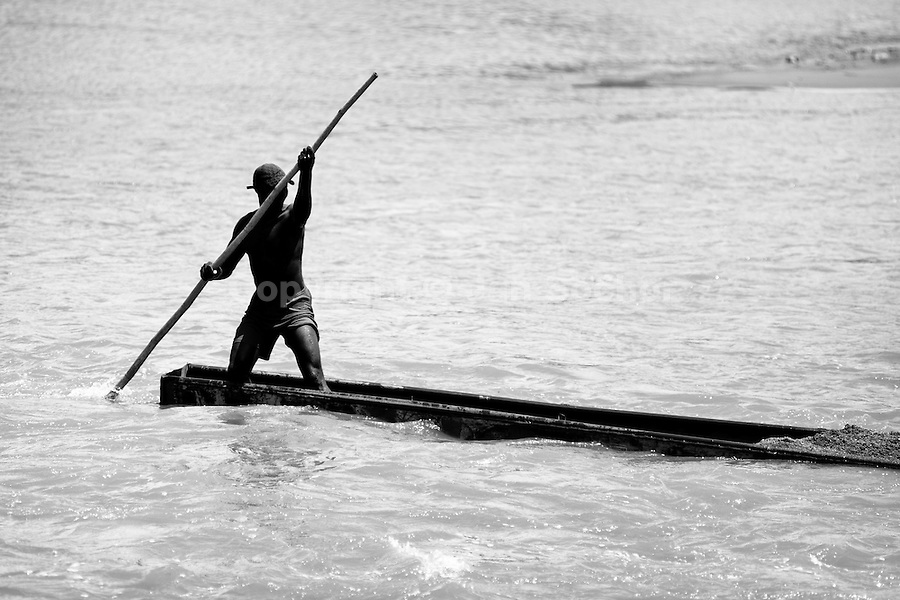 A Colombian sand miner, using a barge pole, navigates his boat loaded with extracted sand in the river La Vieja in Cartago, Colombia, 8 February 2013. Artisanal (unmechanised) sand mining is an ancient mining technique used to obtain sand for construction purposes. Depending on the natural conditions (strength of the stream, depth of the river etc.), together with the sand miners' physical condition, the material is extracted in metal buckets, either by standing on the river bottom and searching for sand by feet, or, diving up to 3-5 meters deep using a wooden plank with steps. In spite of the physically demanding work, a sand miner's daily salary does not exceed 15-20 US dollars. However, the sand miners are very proud of their profession, valuing their work freedom above all, and usually, as long as their health and strength permit, they keep facing the river stream.