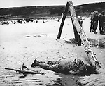 An anonymous American soldier, who died in combat during the Allied invasion, lies on the beach of the Normandy coast, in the early days of June 1944. Two crossed rifles in the sand next to his body are a comrade's last reverence. The wooden structure on the right, normally veiled by high tide water, is an obstruction erected by the Germans to prevent seaborne landings. (AP Photo)