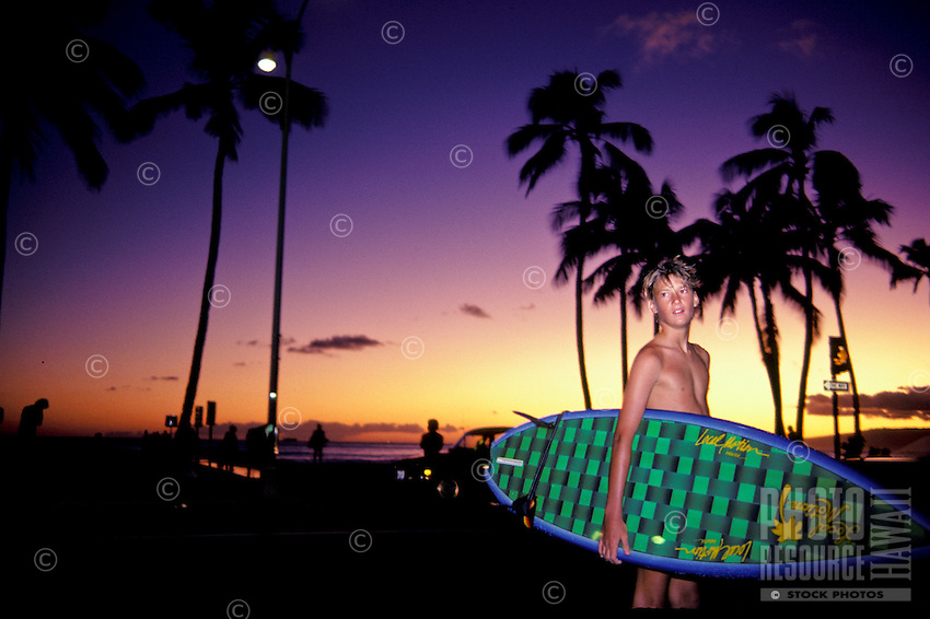 Surfer at Waikiki Beach at sunset with palms in background