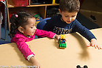 Education Preschool 3 year olds boy and girl playing with small vehicles