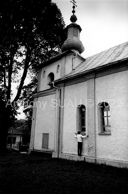Humensky Rokytov, Slovakia Republic.July 1997.An alter boy peers into the church to see if Sunday service is about to finish just in case he needs to sneak back in to do his job..