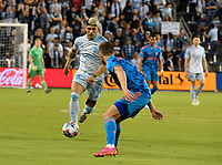 KANSAS CITY, KS - MAY 29: Alan Pulido #9 of Sporting KC tries to get past Adam Lundkvist #3 of Houston Dynamo FC during a game between Houston Dynamo and Sporting Kansas City at Children's Mercy Park on May 29, 2021 in Kansas City, Kansas.