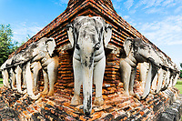 Perspective of elephants and red bricks on a reconstructed pagoda, at Wat Sorasak in Sukhothai Historical Park, Thailand, Southeast Asia