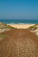 Dirt path leading down to the beach and bright blue sea, Le Porge, Bordeaux, Gironde, France.