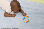 5 month old baby boy African American closeup on stomach reaching for and grasping toy horizontal