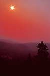 Smoke from Tripod Complex forest fire blankets Chewuk River Valley as sun penetrates at dawn Chewuch River