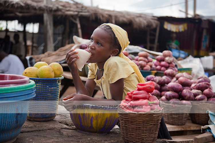 """A young Fulani girl drinks """"kunu"""" from a plastic bag, while manning fruit and vegetable table at a roadside market in Nigeria's Niger State.  Kunu is a delicious millet drink spiced with ginger."""