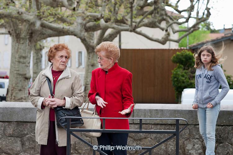 Two women talk in the street in St.Jean du Gard, France.