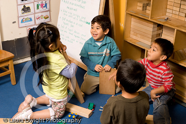 Education Preschool 3-4 year olds group playing in block area horizontal talking and working together