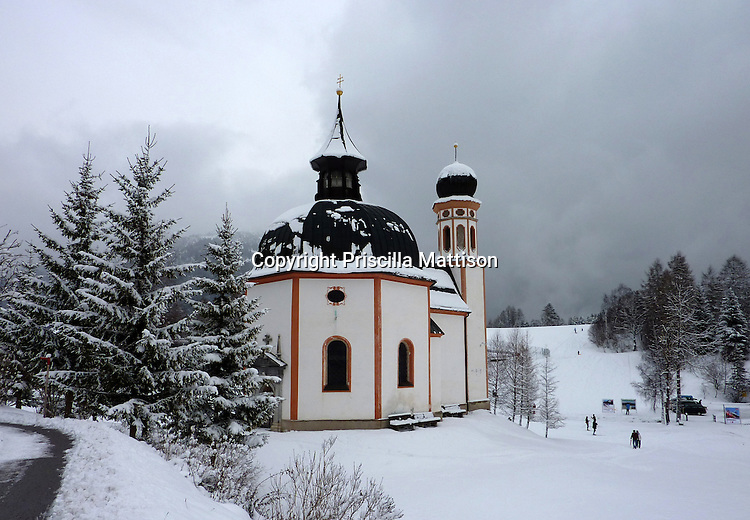 Seefeld, Austria - December 12, 2009:  The Seekirchl (little church in the lake) in Seefeld, Austria, was originally surrounded by an artificial lake; here, by walkers and skiiers.