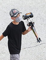 Jul 19, 2020; Clermont, Indiana, USA; A young NHRA fan wearing a mask holds a toy top fuel dragster as he walks through the pits during the Summernationals at Lucas Oil Raceway. Mandatory Credit: Mark J. Rebilas-USA TODAY Sports