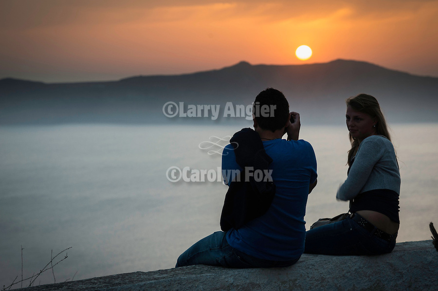 A couple in silhouette photographs the sunset in the fog on the caldera rim, Fira, Santorini