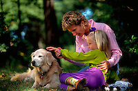 A mother and young girl pet the family Golden Retriever dog.