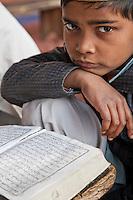 Agra, India.  Young Boy and his Koran, Madrasa of the Jama Masjid (Friday Mosque).