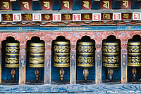 Traditional Buddhist prayer wheels at Changangkha Lhakhang Temple, Thimpu, Bhutan. Buddhists believe that mindfully spinning a prayer wheel produces the same benefits and merits as orally reciting the number of mantras inside the prayer wheel.