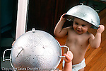 Toddler boy 18 months old looking at reflection in mirror recognizing self wearing metal colander as a hat Caucasian horizontal