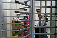 """Palestinian women are seen at the new """"Rechan terminal"""" a modern checkpoint near the Palestinian village of Bartaa, in the West Bank, October 24, 2006. The terminal was constructed to allow Palestinians from the village, which is divided, to move between the two parts of the village, one in the West Bank and the other in Israel.<br /> The new terminal run by Israeli Military Police and with new technology is part of a change in the IDF policy on checkpoints, converting the main checkpoints which separate Israel and the West Bank in new, modern terminals. Photo by Quique Kierszenbaum"""