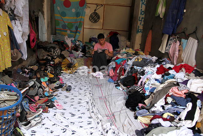 Palestinians looks at second hand clothes at a market in Rafah in the southern Gaza strip, on April 26, 2016. Due to the current economic situation in Gaza Strip, many of the Palestinians resort to meet their needs of used goods. Photo by Abed Rahim Khatib