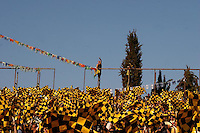 A  Beitar Jerusalem soccer fan, among Betar fans holding yellow and black flags, climbs a poll during the final of the Israeli cup against Macabi Haifa, 2008 - 9. Beitar won the cup in a 3 - 0 result. Beitar Jerusalem FC was founded in the 1930's by the right-wing Revisionist Zionist movement, which later formed the Israeli Likud political party, during the British Mandate rule over Palestine. The chanting of the club is racist and mainly against Arabs. The team is the only one in the Israeli league to have never had an Arab player. Beitar is seen as the right wing and Mizrahi (Jews who came from Asia and Africa) club. Photo by Quique Kierszenbaum