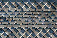 A fine art western abstract of a pattern of wooden, weather-beaten roof shingles with shadows from late afternoon sun.  The triangular shadow patterns contrast against rounded and octagonal patterns, with a diagonal line of nails ascending through the center of the image.