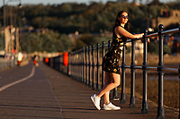 Pictured: Natasha Jenkins takes a stroll during sunrise in Mumbles promenade, near Swansea, Wales, UK. Sunday 13 June 2021<br /> Re: High temperatures and sunshine has been forecast for most of the UK.